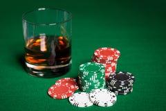 关闭赌博娱乐场芯片和威士忌酒玻璃在桌上 免版税库存图片