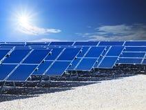 太阳能电池盘区和太阳能量农场供给发光在蓝天动力 库存图片