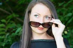 年轻可爱的女孩画象有太阳镜的 免版税库存图片