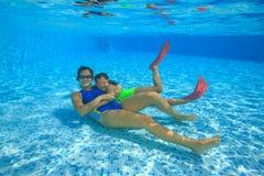 母亲和女儿在游泳池潜水 免版税库存图片