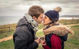 亲吻和拿着杯子热的饮料的年轻夫妇 免版税库存照片