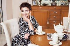 庄重装束的美丽的深色的富有的莽撞的妇女坐一把椅子在一间屋子里用经典内部饮用的酒 免版税库存照片