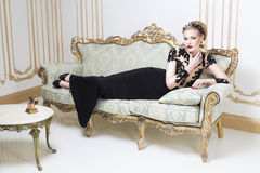 放置在华美的豪华礼服的一个减速火箭的沙发的美丽的白肤金发的皇家妇女 免版税库存图片