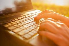 键入在一个膝上型计算机键盘的妇女在一个温暖的晴天户外 图库摄影