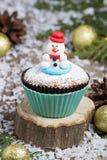 与雪人的欢乐圣诞节杯形蛋糕 免版税库存图片