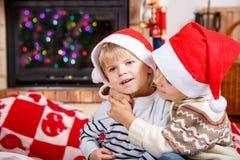 两圣诞老人帽子的小兄弟姐妹男孩画象,室内 免版税图库摄影
