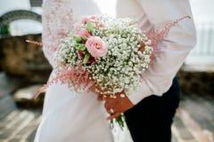 在新郎的和新娘的手特写镜头的婚礼花束 图库摄影