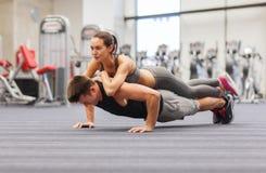 做在健身房的微笑的夫妇俯卧撑 免版税库存照片