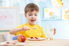 Παιδί που τρώει τα υγιή τρόφιμα στο σπίτι Στοκ φωτογραφία με δικαίωμα ελεύθερης χρήσης