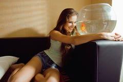 在家使用与金鱼的俏丽的妇女, 免版税库存图片