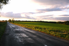 Εθνική οδός με τα θυελλώδη σύννεφα στην αγροτική σκηνή ηλιοβασιλέματος Στοκ φωτογραφία με δικαίωμα ελεύθερης χρήσης
