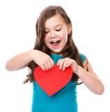 幸福-有红色心脏的微笑的女孩 免版税图库摄影
