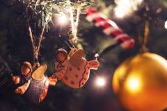 垂悬在圣诞树的两个五颜六色的天使 免版税库存图片