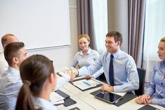 见面在办公室的小组微笑的商人 免版税库存照片