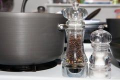 由罐的盐和胡椒研磨机在煤气炉 免版税库存照片