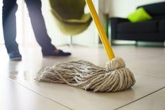 做差事的妇女在家清洗在拖把的地板焦点 免版税库存图片