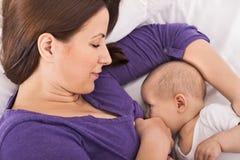 哺乳她的小婴儿的微笑的愉快的母亲 免版税库存照片