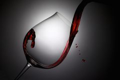 红葡萄酒涌入了与下落的一个酒杯 免版税库存图片