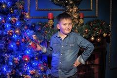 一件牛仔布衬衣的男孩反对圣诞树 免版税图库摄影