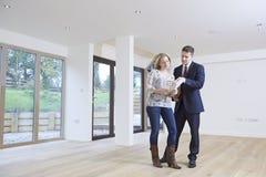 Агент по продаже недвижимости показывая предполагаемого женского покупателя вокруг свойства Стоковое Изображение