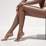 美好的妇女棕褐色腿 对白色墙壁 免版税库存图片