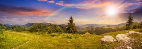 在山坡草甸的冰砾在日落的山的与彩虹 免版税库存照片
