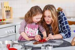 母亲和小孩女孩烘烤圣诞节的姜饼曲奇饼 图库摄影