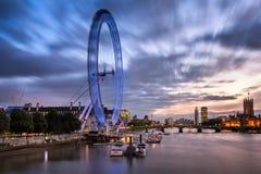 伦敦眼和威斯敏斯特桥梁在晚上,英国 免版税库存图片