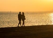 Ρομαντικός περίπατος κατά μήκος της παραλίας στο ζεύγος ηλιοβασιλέματος Στοκ Εικόνες