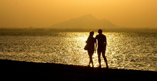 沿海滩的浪漫漫步在日落夫妇 免版税库存照片