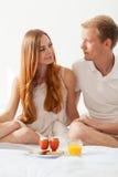 年轻夫妇在食用的床上早餐 免版税库存照片