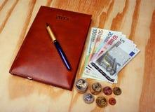 金钱欧洲日历笔记和笔 免版税库存照片