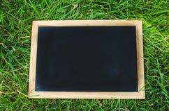 在绿草的空白的黑板 免版税库存图片