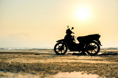 现出轮廓在海滩的摩托车立场 免版税库存图片