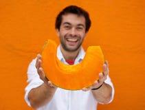 微笑和拿着切片橙色南瓜的年轻人 免版税库存照片