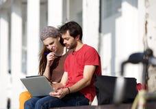 坐在校园的两名学生一起看膝上型计算机 免版税库存照片