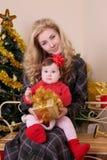 母亲和女婴当圣诞老人帮手在圣诞节 免版税库存图片