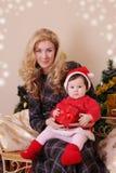 母亲和女婴当圣诞老人帮手在圣诞节 免版税图库摄影
