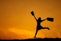 拿着购物袋的愉快的妇女跳跃在日落剪影 免版税库存照片