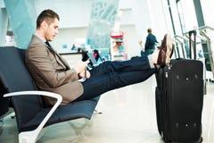 商人在带着智能手机和手提箱的机场 免版税库存照片