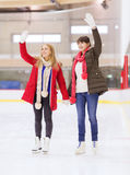 Ευτυχείς φίλοι κοριτσιών που κυματίζουν τα χέρια στην αίθουσα παγοδρομίας πατινάζ Στοκ Φωτογραφίες