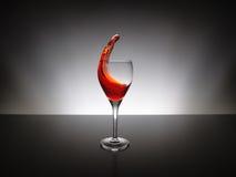 倾倒在玻璃之上的红葡萄酒 免版税库存图片