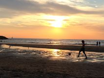 踢足球的男孩在海滩在日落 免版税图库摄影