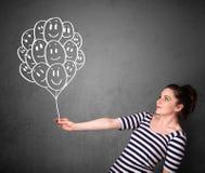 Женщина держа пук усмехаясь воздушных шаров Стоковое Изображение RF
