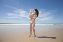 有婴孩的比基尼泳装妈咪海滩的 免版税库存照片