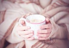 热的咖啡温暖在女孩的手上的杯 免版税库存图片