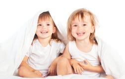 愉快的小女孩在床上孪生姐妹在一揽子下获得乐趣 免版税库存图片