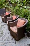 藤条椅子和藤条咖啡桌与绿色树在室外 免版税图库摄影