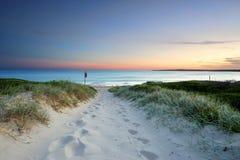 在黄昏日落澳大利亚的沙滩足迹 免版税库存照片