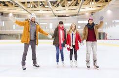 Ευτυχείς φίλοι που κυματίζουν τα χέρια στην αίθουσα παγοδρομίας πατινάζ Στοκ Εικόνες